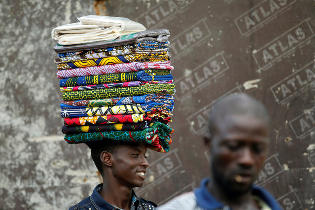 "A man selling unsewn fabrics locally known as ""Ankara"" walks past through a street at Agege district in Lagos, Nigeria June 22, 2016. (Photo by Akintunde Akinleye/Reuters)"