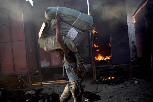 A man walks carrying sacks with goods next to remains of a fire in a market of Port-au-Prince, Haiti on January 14, 2020. (Photo by Andres Martinez Casares/Reuters)
