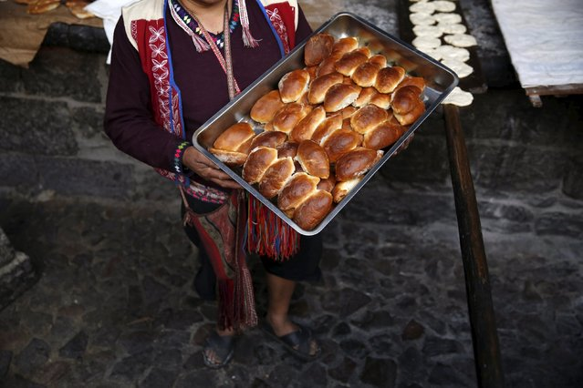 Baker Eulogio Pillco shows traditional empanadas that he baked using an oven made of clay in the town of Pisac, Cusco, August 13, 2015. (Photo by Pilar Olivares/Reuters)