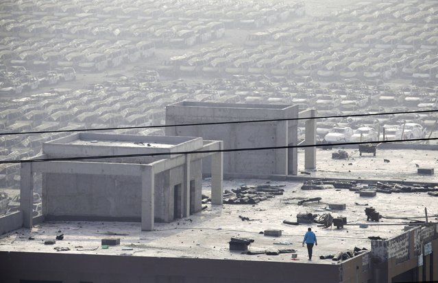 A man works on the roof of a building near the site of Wednesday night's explosions at Binhai new district on a hazy day in Tianjin, China, August 15, 2015. (Photo by Jason Lee/Reuters)