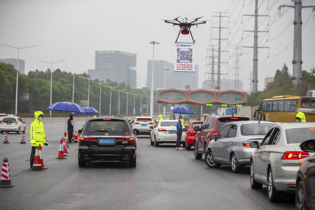 In this Tuesday, February 11, 2020, photo released by China's Xinhua News Agency, a drone carries a QR code placard near an expressway toll station in Shenzhen in southern China's Guangdong Province. As a measure to help prevent and control novel coronavirus, an online register system for vehicles coming back to Shenzhen has been put into use since Feb. 8. To increase the efficiency, local police officers used drones to carry a QR code at the expressway exits for drivers to get registered with less contact with other people. (Photo by Lai Li/Xinhua via AP Photo)