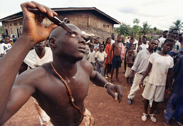 """A young man forces the blade of a knife into his eye as a show of his mystical powers to the people in his village Badasso, Ivory Coast (50 miles north of the capital city Abidjan), Saturday, June 15, 1996. The Abidjis ethnic group hold an annual ceremony called """"Dipris"""" to demonstrate their physical and mystical powers and to honor their ancestors who pass on these strengths from the dead. Beginning from early morning citizens of Badasso walk the streets in a trance like state. Men, who believe they are immune to pain and injury, plunge knives into their bodies and women writhe on the ground possessed by the spirits of their ancestors. (Photo by David Guttenfelder/AP Photo)"""