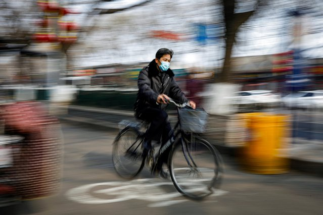 A man wearing a face mask rides a bicycle, as the country is hit by an outbreak of the novel coronavirus, in Beijing, China on February 12, 2020. (Photo by Carlos Garcia Rawlins/Reuters)