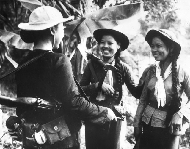 1966: Three young women from South Vietnam with rifles on their shoulders