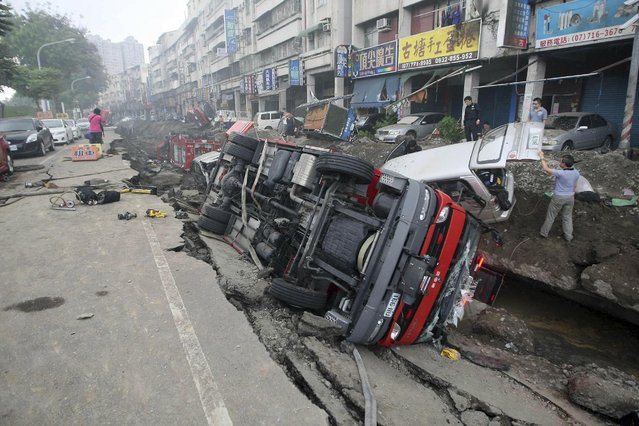 People inspect vehicles tipped over following multiple explosions from an underground gas leak in Kaohsiung, Taiwan, early Friday, August 1, 2014. (Photo by AP Photo)