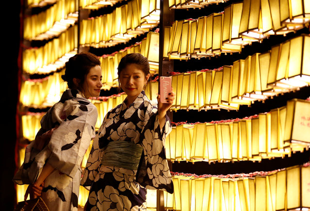 Women in yukatas, or casual summer kimonos, take their selfie in front of paper lanterns during the annual Mitama Festival at the Yasukuni Shrine, where more than 2.4 million war dead are enshrined, in Tokyo, Japan July 13, 2017. (Photo by Kim Kyung-Hoon/Reuters)