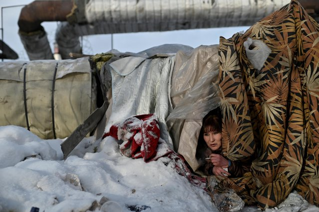 Galiya, 29, who is homeless, looks out from Alexey's makeshift shelter in Omsk, Russia, February 14, 2020. (Photo by Alexey Malgavko/Reuters)
