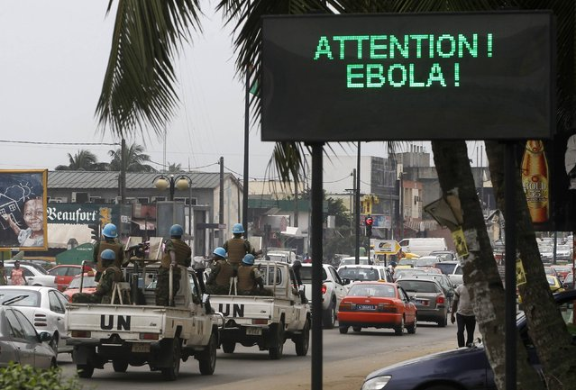 A U.N. convoy of soldiers passes a screen displaying a message on Ebola on a street in Abidjan August 14, 2014. The world's worst outbreak of Ebola has claimed the lives of 1,069 people and there are 1,975 probable and suspected cases, the vast majority in Guinea, Liberia and Sierra Leone, according to new figures from the World Health Organisation (WHO). Ivory Coast has recorded no cases of Ebola. (Photo by Luc Gnago/Reuters)