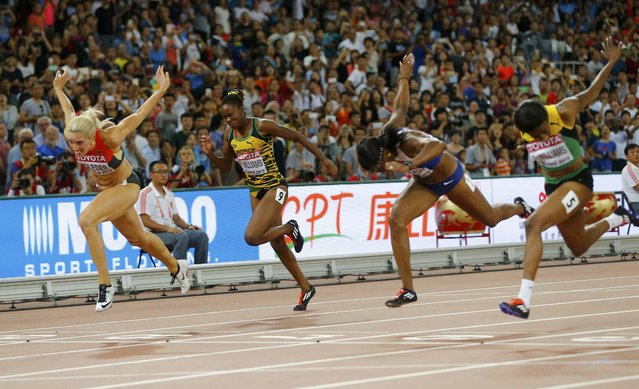 Second placed Cindy Roleder of Germany (L) crosses the finishi line to win silver at the women's 100 metres hurdles final during the 15th IAAF World Championships at the National Stadium in Beijing, China, August 28, 2015. (Photo by Kai Pfaffenbach/Reuters)