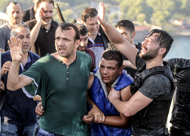 People apprehend a Turkish soldier, center in blue, that participated in the attempted coup, on Istanbul's Bosporus Bridge, Saturday, July 16, 2016. (Photo by Selcuk Samiloglu/AP Photo)