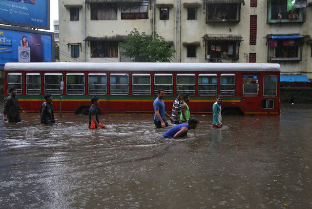People wade through a water-logged road past a stalled passenger bus during rains in Mumbai, August 29, 2017. (Photo by Shailesh Andrade/Reuters)