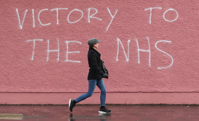 A woman walks past graffiti in support of NHS workers, on a wall of the Royal Victoria Hospital in Belfast, Northern Ireland on April 2, 2020. (Photo by Niall Carson/PA Images via Getty Images)