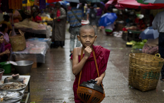 A novice Buddhist monk walks in a street market to collect alms in the rain following a cleric's rule of no footwear nor use of umbrellas in Yangon, Myanmar, Thursday, August 21, 2014. Downpours during the monsoon season are intense, and often more than 100 millimeters (3.9 inches) of rain falls in an hour resulting in flash floods and traffic jams. (Photo by Gemunu Amarasinghe/AP Photo)