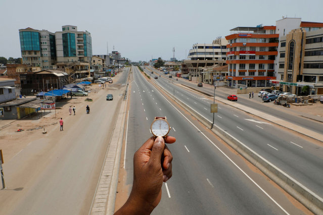 A watch showing the time at noon, is displayed for a photo as people walk past Ring Road Central Street, which is almost empty during the coronavirus disease (COVID-19) outbreak, in Accra, Ghana, March 31, 2020. (Photo by Francis Kokoroko/Reuters)
