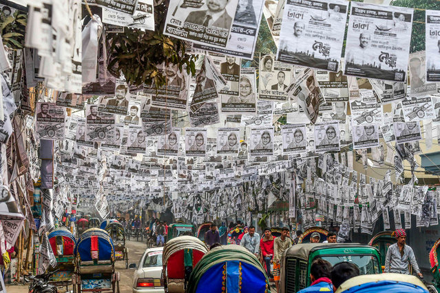 In this photograph taken on January 29, 2020, commuters make their way on a street adorned with election posters laminated with plastic in Dhaka, Bangladesh. Dhaka is awash with an estimated 304 million plastic-laminated posters ahead of elections in the Bangladeshi capital, and environmentalists are up in arms. (Photo by Munir Uz Zaman/AFP Photo)
