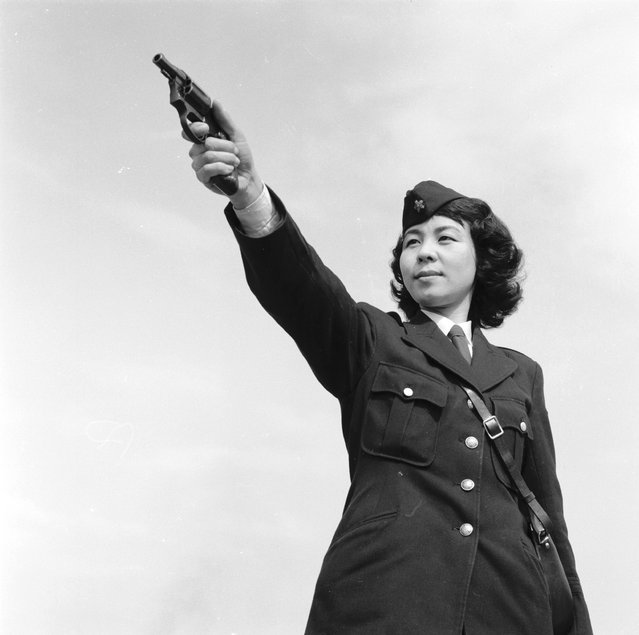 Tokyo policewoman Haruko Tanaka of the Asakusa ward aims her gun during shooting practice, circa 1955.  (Photo by Evans/Three Lions)