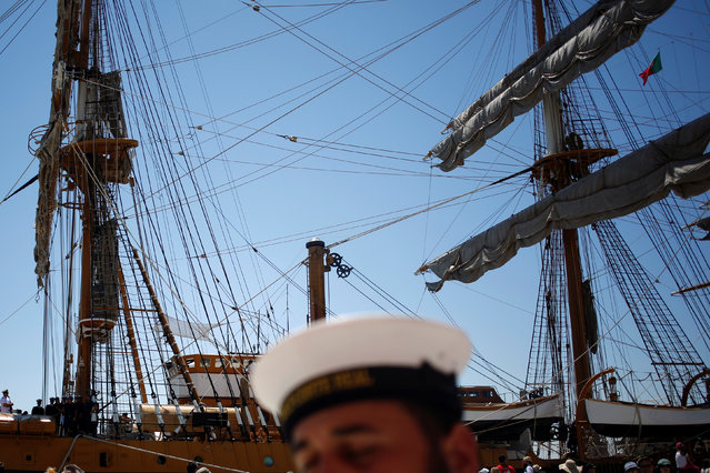 A crew member passes by a ship before the beginning of the Tall Ships Races 2016 parade, in Lisbon, Portugal, July 25, 2016. (Photo by Pedro Nunes/Reuters)
