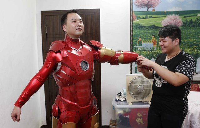 Zhang Licheng, with the help of his friend, puts on his home-made Iron Man armour at his home in Jiaxing, Zhejiang province, August 25, 2014. Using 3,000 yuan (488 USD) and infomation gathered online, Zhang took half a year to make the armour, which he made to please his three-year-old son, according to local media. (Photo by Reuters/Stringer)