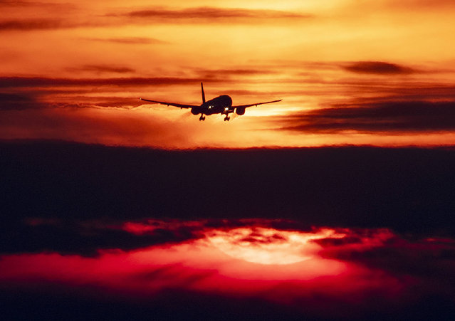 An aircraft approaches the international airport in Frankfurt, Germany, as the sun rises on Wednesday, August 28, 2019. (Photo by Michael Probst/AP Photo)