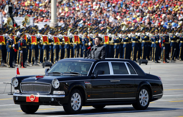 Chinese President Xi Jinping stands in a car to review the army during a parade commemorating the 70th anniversary of Japan's surrender during World War II held in front of Tiananmen Gate in Beijing, Thursday, September 3, 2015. The spectacle involved more than 12,000 troops, 500 pieces of military hardware and 200 aircraft of various types, representing what military officials say is the Chinese military's most cutting-edge technology. (Photo by Ng Han Guan/AP Photo)