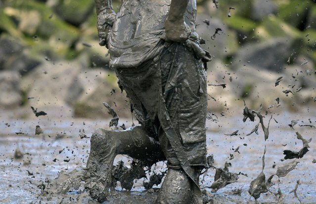 """A participant holds his pant during a handball match at the so called """"Wattoluempiade"""" (Mud Olympics) in Brunsbuettel at the North Sea, Germany July 30, 2016. (Photo by Fabian Bimmer/Reuters)"""