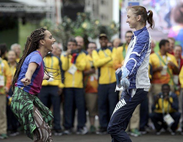 Azerbaijani gymnast Marina Durunda (R) dances with a performer at the Olympic Village in Rio de Janeiro, Brazil on August 3, 2016. (Photo by Alkis Konstantinidis/Reuters)