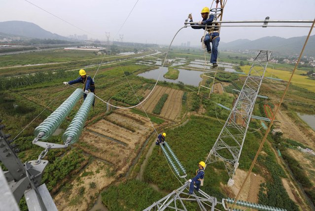 Workers install cables on a electricity pylon above fields of crops in Xihu township of Tongling, Anhui province September 9, 2014. Chinese Premier Li Keqiang said on Monday that China's economy could grow by around 7.5 percent this year as targeted by the government, but reiterated Beijing's view that a healthy job market was more important than delivering a certain level of economic growth. (Photo by Reuters/China Daily)
