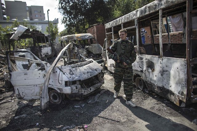A pro-Russian rebel walks past burnt-out vehicles in an area that was recently shelled in Donetsk, eastern Ukraine, September 16, 2014. (Photo by Marko Djurica/Reuters)