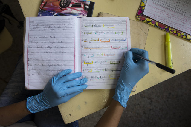 """A teacher wearing surgical gloves as a precaution against the spread of the new coronavirus, corrects a student's homework at the """"Fe y Alegria"""", or Faith and Happiness school, closed to in-class instruction due to the government lockdown in Caracas, Venezuela, Tuesday, May 12, 2020. The children's homework is brought to the school by their parents who do not have access to the internet, making it impossible for their children to receive online instruction. (Photo by Ariana Cubillos/AP Photo)"""