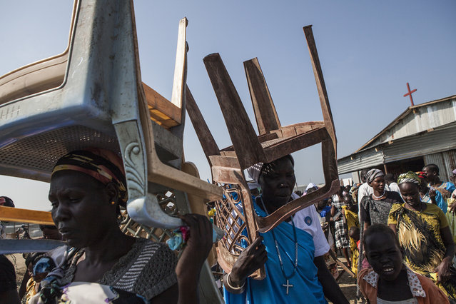 Church members carry out chairs and benches after service at the Dolieb Hill Presbyterian Church in the Protection of Civilians (POC) site at the United Nations Mission in South Sudan (UNMISS) compound in Malakal, South Sudan on Sunday, July 10, 2016. (Photo by Jane Hahn/The Washington Post)