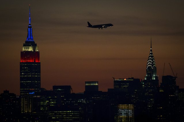 A plane preparing to land at LaGuardia is pictured between the Empire State building, lit in traditional red, white and blue to commemorate 9/11, and the Chrysler building in New York September 11, 2015. (Photo by Carlo Allegri/Reuters)