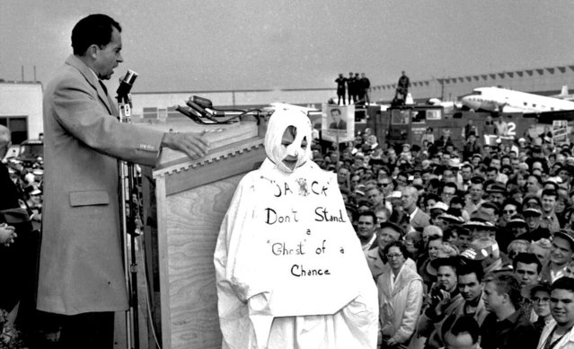 """Vice President Richard M. Nixon addresses a crowd at Chicago's O'Hare Airport, October 29, 1960, while campaigning for president against Sen. John F. Kennedy. Next to him stands 10-year-old Tom Lemke, wearing a Halloween ghost costume that reads """"Jack Don't Stand a Ghost of a Chance"""", referring to John F. Kennedy. When Nixon spotted to boy in the crowd, he called attention to the youngster. (Photo by AP Photo)"""