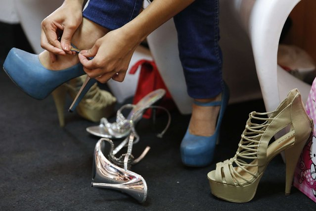 A girl tries on stilettos to find the right size during a class at a modelling academy in Caracas September 20, 2014. (Photo by Carlos Garcia Rawlins/Reuters)