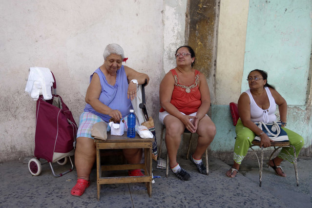 A woman sells cigars, plastic bags and women's sanitary napkins, left, on the sidewalk alongside other women in Havana, Cuba, Tuesday, May 24, 2016. (Photo by Desmond Boylan/AP Photo)