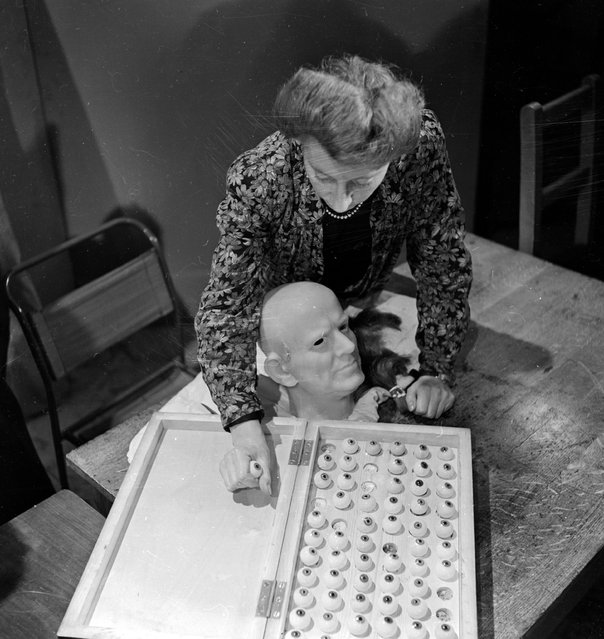 Vera Bland chooses the right colour eyeballs for a wax head of Cardinal Bernard Griffin, Archbishop of Westminster in the workshop of Madame Tussaud's, London, June 1946. (Photo by George Konig/Keystone Features)