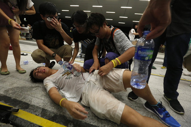 """A protester receives help after being pepper sprayed during a confrontation with the police, following a rally for the October 1 """"Occupy Central"""" civil disobedience movement in Hong Kong September 27, 2014. (Photo by Bobby Yip/Reuters)"""