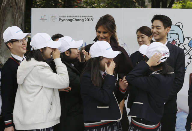 """U.S. first lady Melania Trump is greeted by South Korean middle school students as Choi Min-ho, a member of South Korean boy band Shinee, top right, watches during """"Girls Play 2!"""" Initiative, an Olympic public diplomacy outreach campaign, at the U.S. Ambassador's Residence in Seoul, South Korea, Tuesday, November 7, 2017. (Photo by Ahn Young-joon/AP Photo)"""