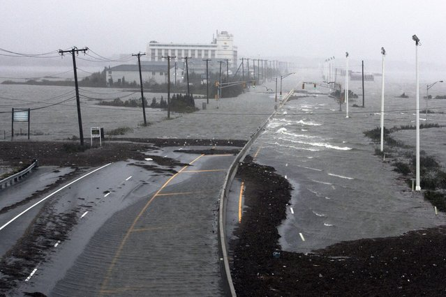 U.S. Route 30, the White Horse Pike, one of three major approaches to Atlantic City, New Jersey, is covered with water from Absecon Bay in this view looking west, during the approach of Hurricane Sandy, October 29, 2012. Hurricane Sandy began battering the U.S. East Coast on Monday with fierce winds and driving rain, as the monster storm shut down transportation, shuttered businesses and sent thousands scrambling for higher ground hours before the worst was due to strike. (Photo by Tom Mihalek/Reuters)