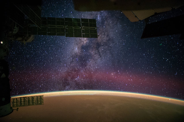 """In this photo provided by NASA astronaut Reid Wiseman captured this image from the International Space Station and posted it to social media on Sept. 28, 2014, writing, """"The Milky Way steals the show from Sahara sands that make the Earth glow orange"""". (Photo by Reid Wiseman/AP Photo/NASA)"""