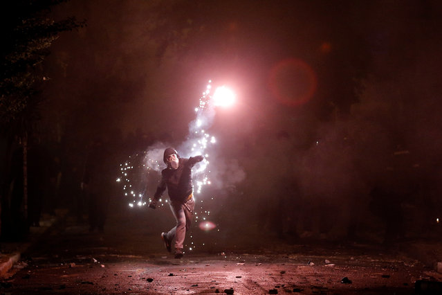 A hooded protester throws a flare during clashes following a rally marking the 44th anniversary of a 1973 student uprising against the military dictatorship that was ruling Greece, in Athens, Greece on November 17, 2017. (Photo by Alkis Konstantinidis/Reuters)