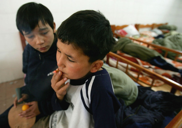 Maimaiti Aili (R), a 13-year old boy from China's Xinjiang Uygur Autonomous Region, smokes at an assistance center February 24, 2005 in Shenzhen, Guangdong Province, China. Aili was kidnapped and taken to Shenzhen by a gang leader and made to steal for him. (Photo by Cancan Chu/Getty Images)