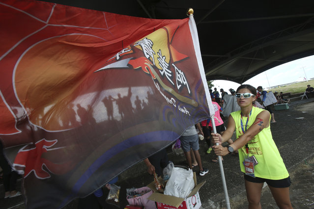 A boat crew member holds a team flag during the traditional Chinese dragon boat race in Taipei, Taiwan, Thursday, June 25, 2020. Dragon boat races are in remembrance of Chu Yuan, an ancient Chinese scholar-statesman, who drowned in 277 B.C. while denouncing government corruption. (Photo by Chiang Ying-ying/AP Photo)