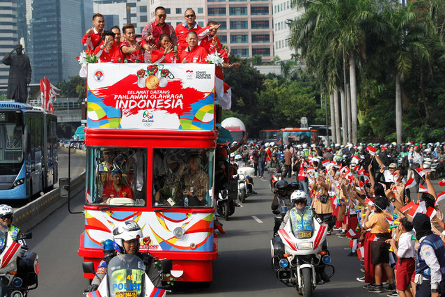 Indonesia's Rio Olympics medallists ride an open-top bus with coaches and officials on their way to meet with President Joko Widodo in Jakarta, Indonesia August 24, 2016. (Photo by Iqro Rinaldi/Reuters)
