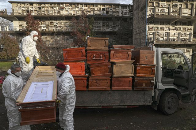 Workers collect and stack the coffins of people that have been recently cremated amid the new coronavirus pandemic, at the La Recoleta cemetery in Santiago, Chile, Sunday, June 28, 2020. The coffins are collected, destroyed, and processed by a company specialized in organic waste. (Photo by Esteban Felix/AP Photo)