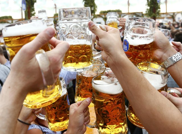 Visitors toast with beer on the first day of the 182nd Oktoberfest in Munich, Germany, September 19, 2015. (Photo by Michaela Rehle/Reuters)
