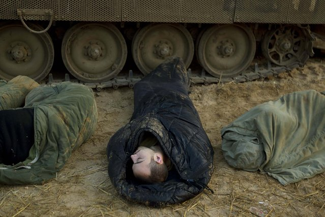 Israeli soldiers sleep next to their armored personal carriers in a staging area in southern Israel on Monday. (Photo by Ariel Schalit/Associated Press)