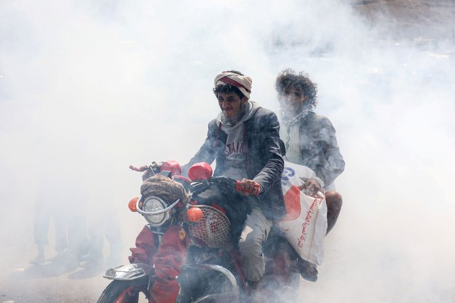People ride a motorbike amidst smoke from fumigation during a fumigation campaign while the spread of the coronavirus disease (COVID-19) continues, on the outskirts of Sanaa, Yemen on April 13, 2020. (Photo by Khaled Abdullah/Reuters)