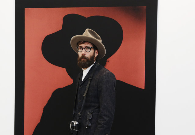 """A visitor poses with artist John Stezaker's artwork """"Shadow"""" at the Frieze Art Fair in London, October 14, 2014. (Photo by Luke MacGregor/Reuters)"""