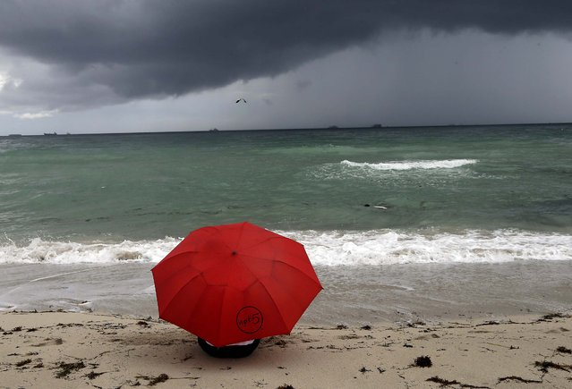 A beachgoer sits under an umbrella as storm clouds gather in the distance,Tuesday, September 23, 2014, in Miami Beach, Fla. According to weather reports, there is an eighty percent chance of rain in South Florida Tuesday. (Photo by Lynne Sladky/AP Photo)
