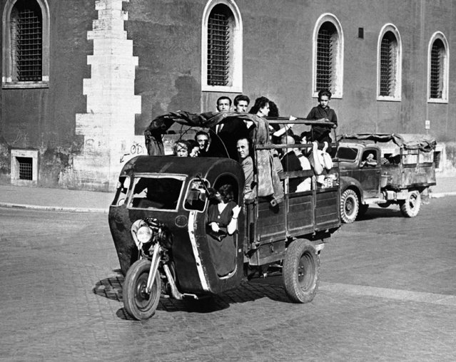 """The famous Seven Hills of Rome, present citizens of the Italian capital with a serious problem of transportation. The Germans looted most of Rome's motor buses, and the taxis have been requisitioned by the Allied commission leaving only a few trolley-buses and street cars which do not connect all parts of the city. Many strange contrivances are therefore to be seen running the streets, helping to convey Romans from place to place in the capital. The three wheel truckbed vehicle is called """"motofurgoncino"""" and carries passengers who stand and sit in the back, in Rome on October 11, 1945. During rush hours two passengers, one on either side, ride with the driver. (Photo by AP Photo)"""